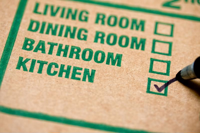 Box label noting whether the container belongs in the living room, dining room, bathroom or kitchen with the latter marked.