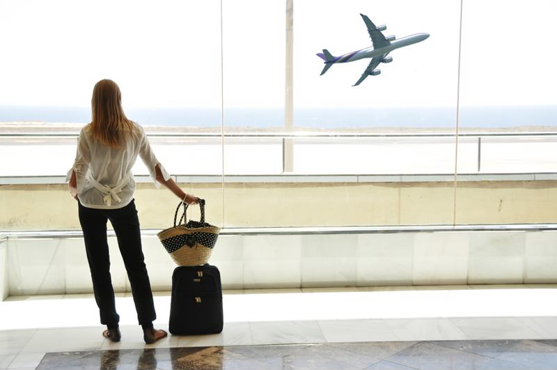 Young woman standing in an airport watching a plane take off.