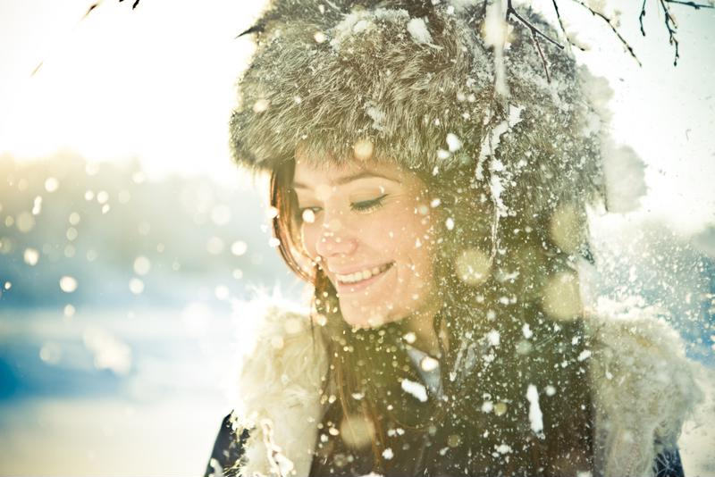 A woman smiling as snow falls down around her.