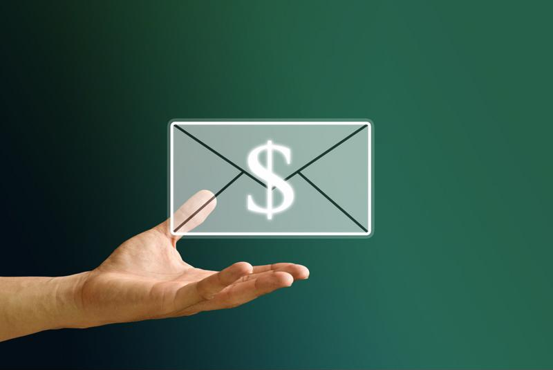 An email with adollar sign over it and a hand holding the email.
