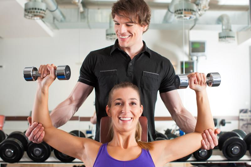Woman lifting weights with help of personal trainer.