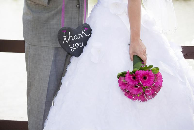 Bride and groom with thank you sign.