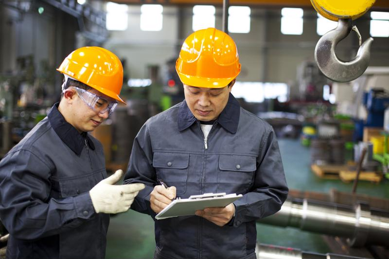 Picture of two Chinese factory workers standing and talking inside a manufacturing facility in China