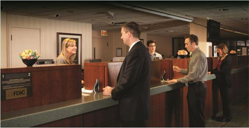 A man stands in line at a bank.