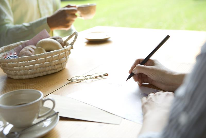 A woman writing a letter at a table.