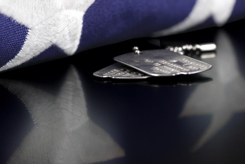 military dog tags set beside blue field of the American flag