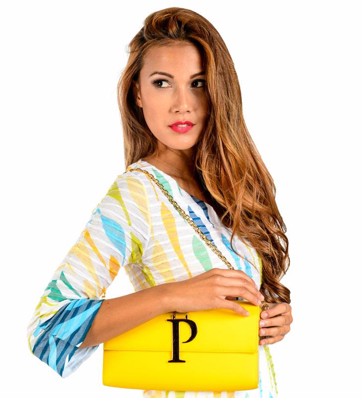 Woman holding a yellow purse with a P on it.