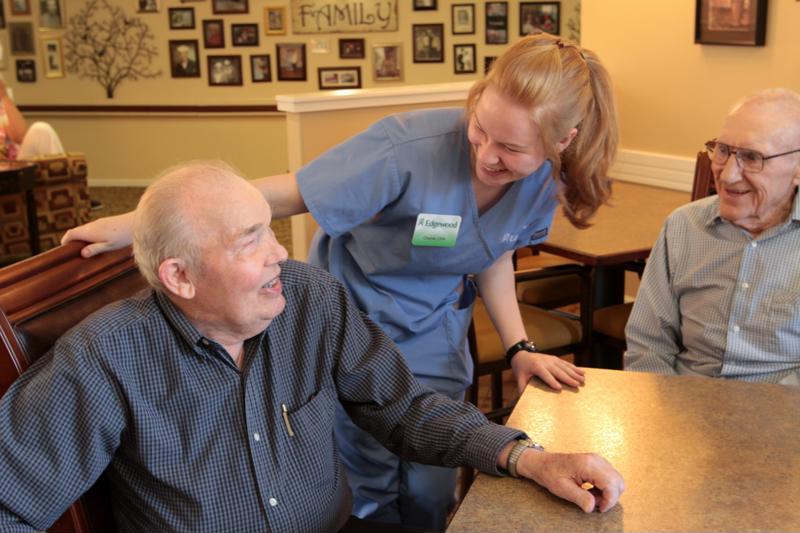 Edgewood staff member leaning over senior resident.