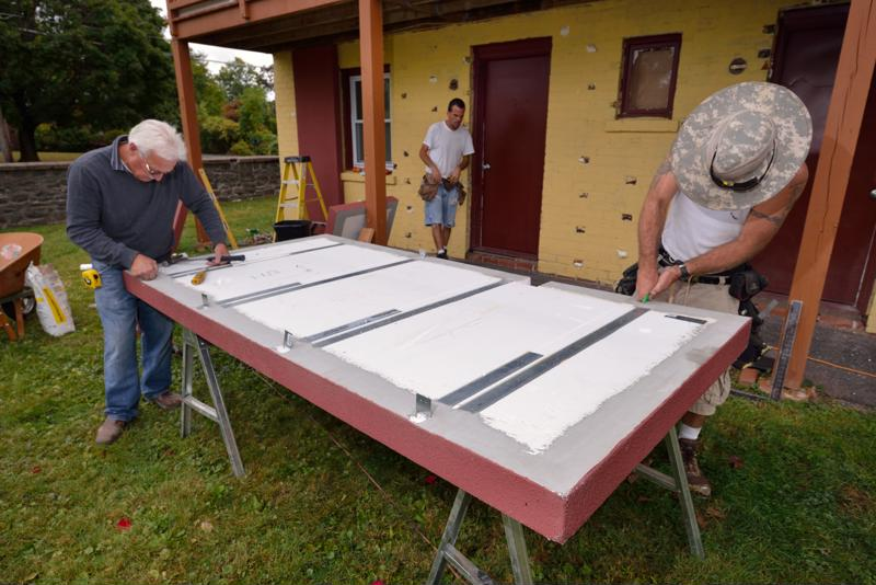 The construction team prepares wall panels for installation.