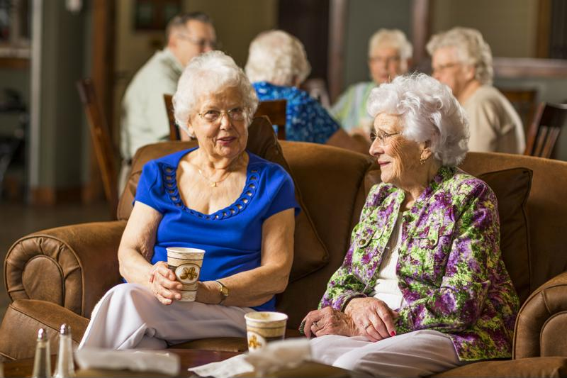 Two senior women drinking coffee on couch.