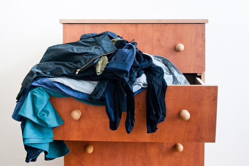 Messy dresser filled with dangling clothes.