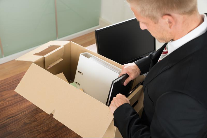 Man packing his office supplies into a box.