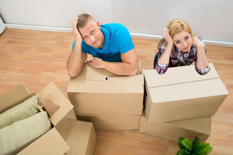 Couple with moving boxes looking frustrated.