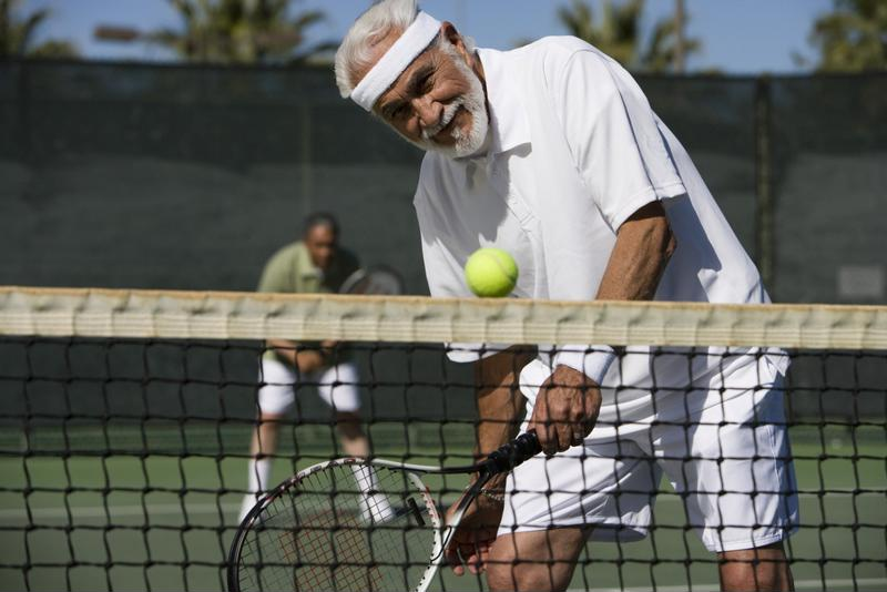 Senior man playing tennis.