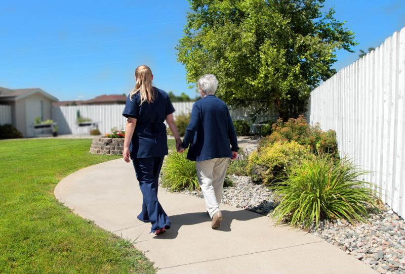 Senior and staff walking at community center.