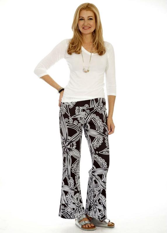Woman wearing patterned pallazzo pants and a white shirt.