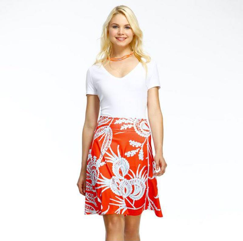 A young woman wearing a bright, tropical print skirt.