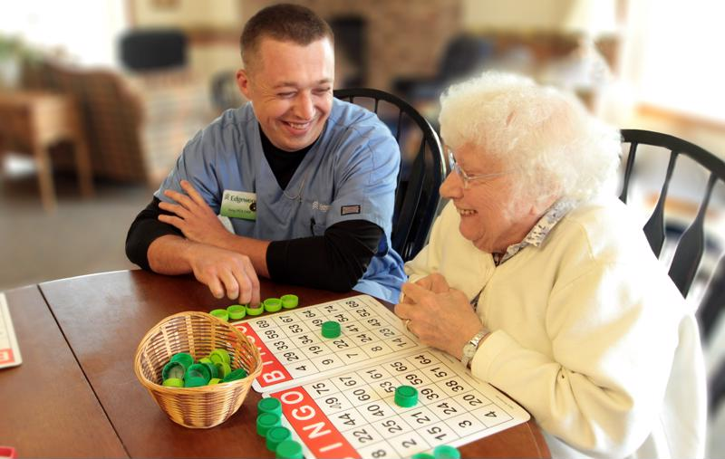 Edgewood senior living staff playing bingo with senior.