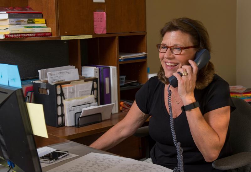 Cheryl talks on the phone with a customer.