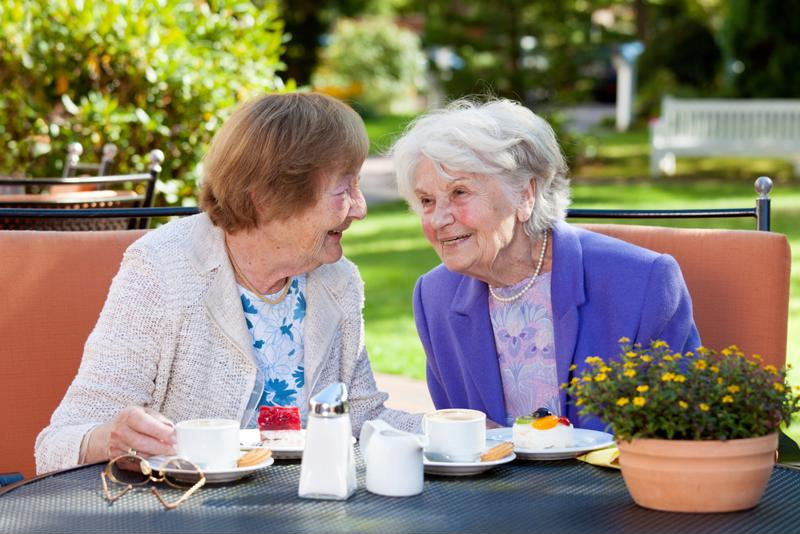 Two seniors socializing at lunch on outdoor patio.