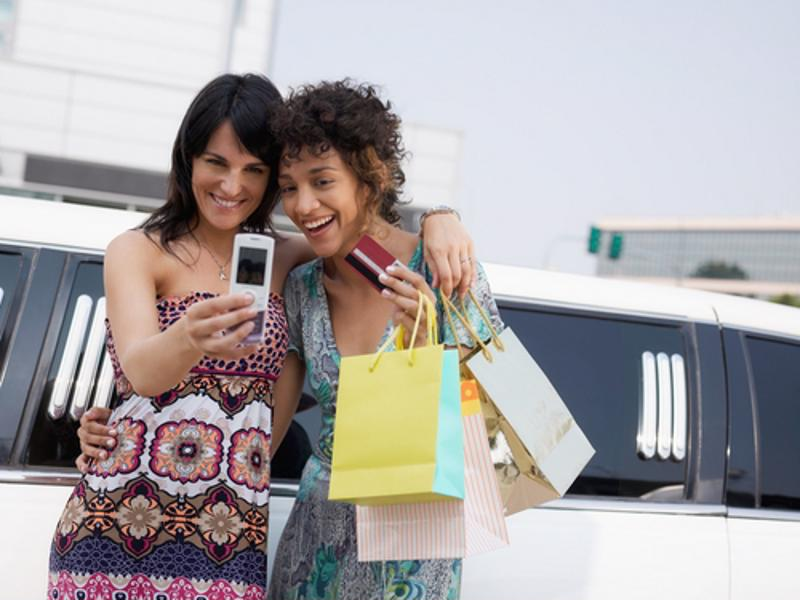 Friends use phones to take pictures while shopping.