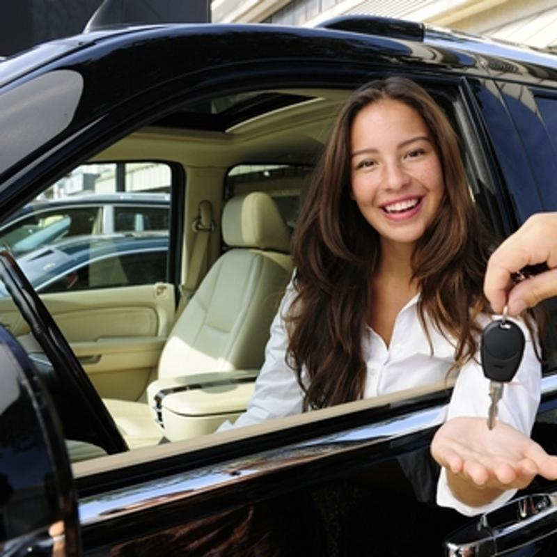A woman receives the keys to a new car.