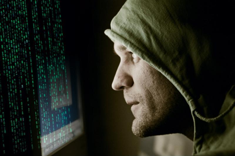 Computer hacker peering  at PC screen.