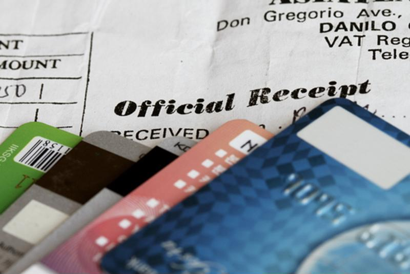 Credit cards piled on top of one another over a bill or receipt.