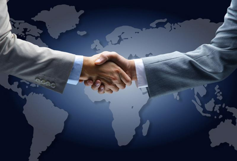 A handshake on a world map.