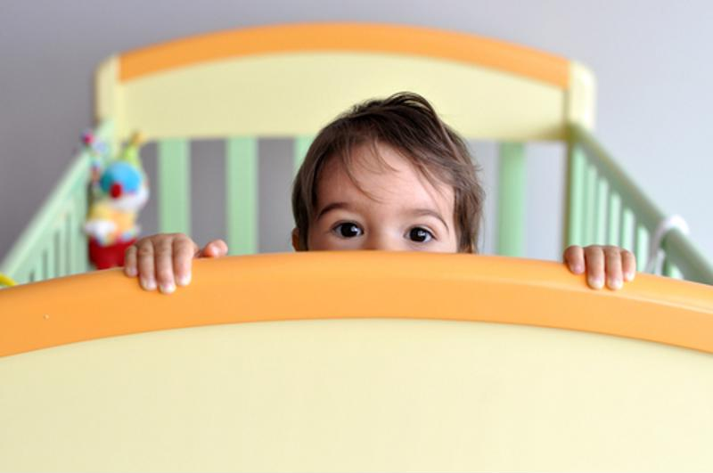 A child peeking over a crib.
