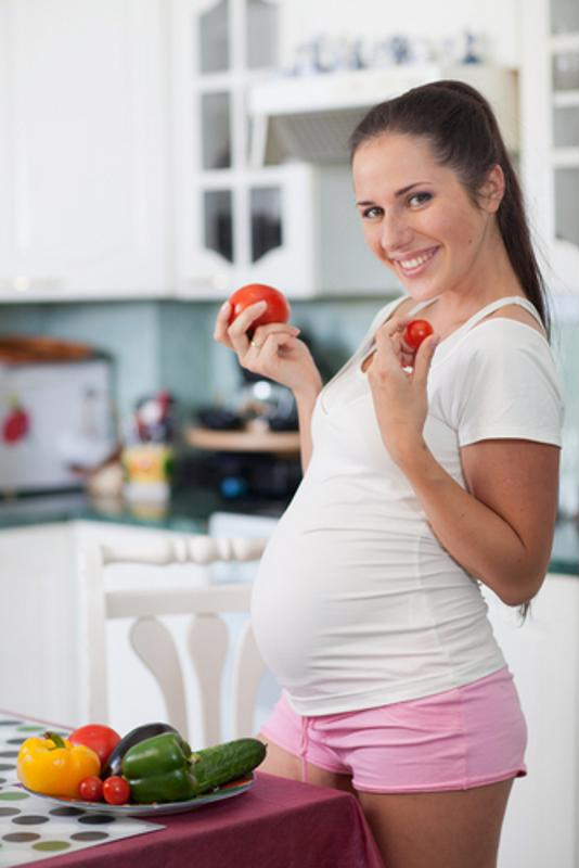 A pregnant woman posing with fresh fruits and vegetables.