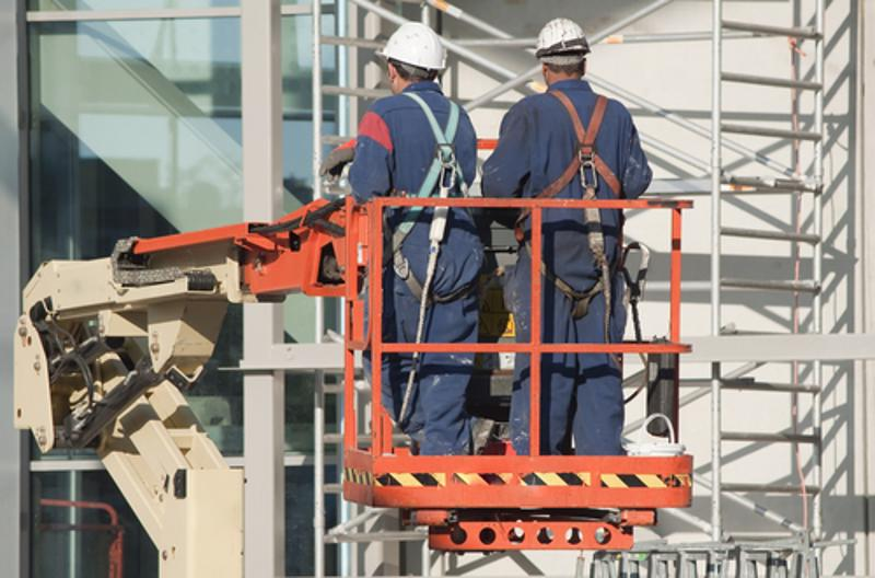 Two workers with PPE on cherry picker.