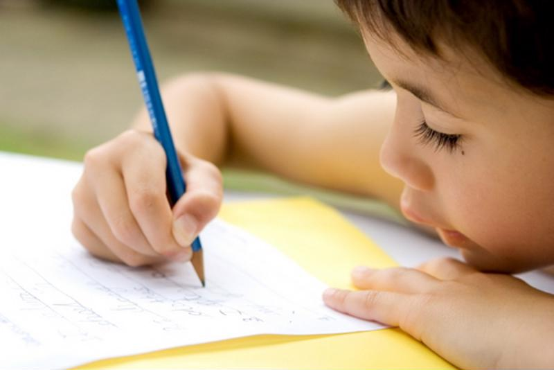 A young boy writing on a piece of paper.