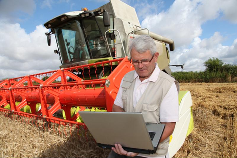 Farmer checking his laptop with farming equipment behind him.