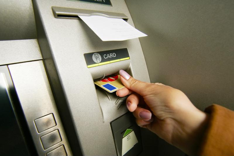 Person inserting card in ATM.