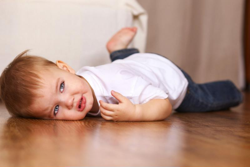 A child throwing a tantrum on the floor.