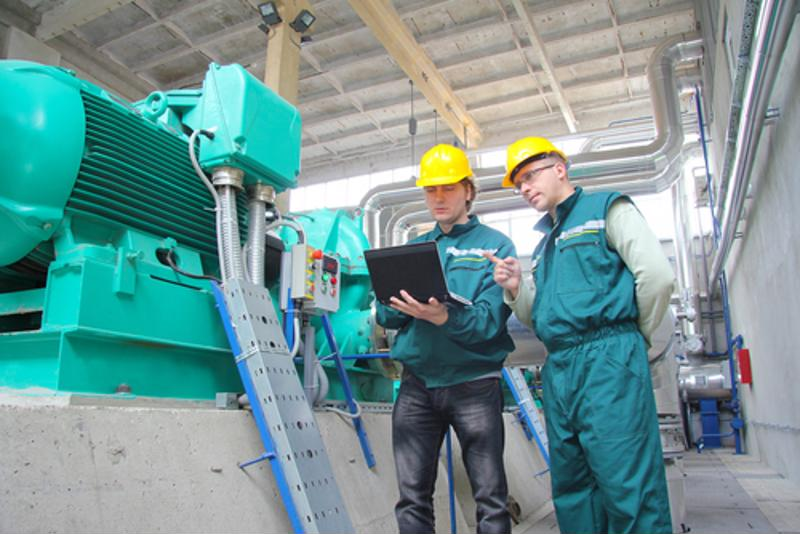 Two factory workers inspect machinery