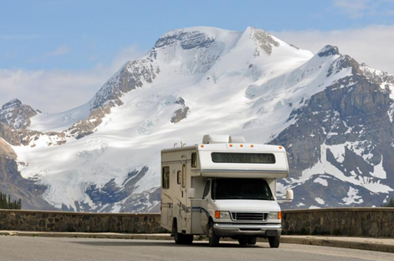 An RV drives past a snow-covered mountain