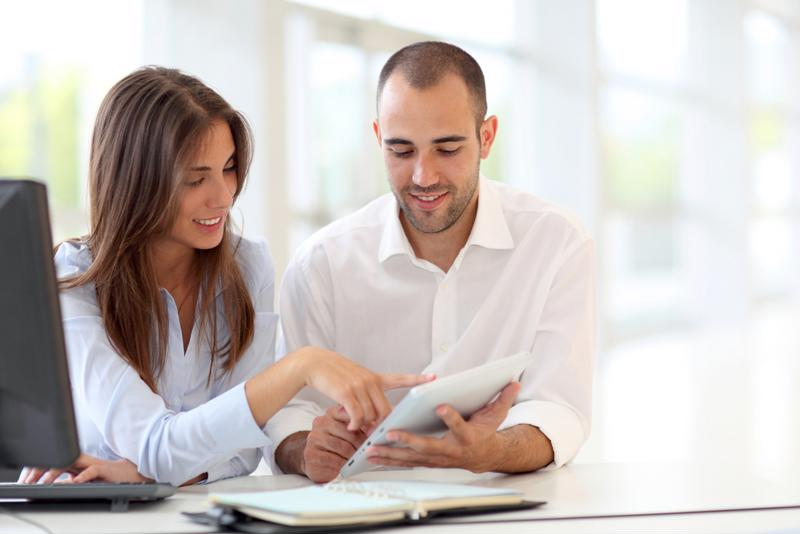 Young smiling couple looking at a tablet.