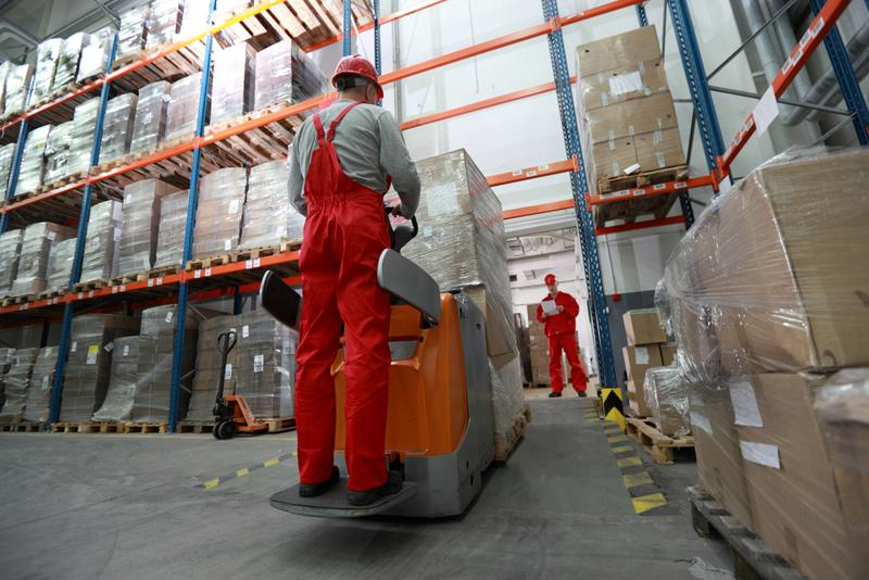 Workers move goods in a warehouse.