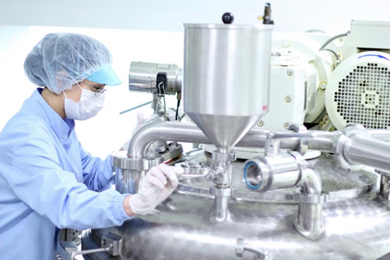 An operator works with stainless steel pharmaceutical equipment.