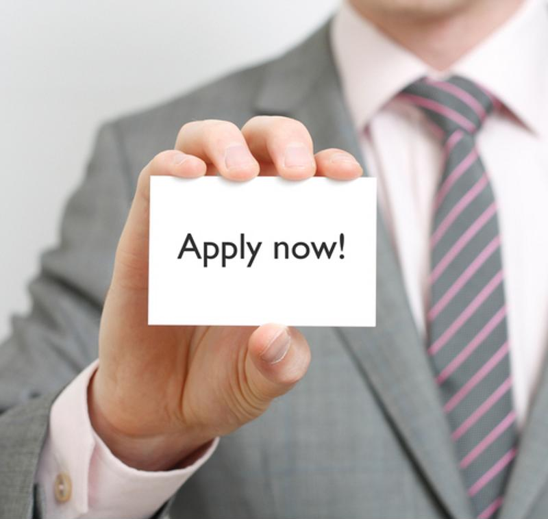 Man in suit and tie holding 'apply now' card.