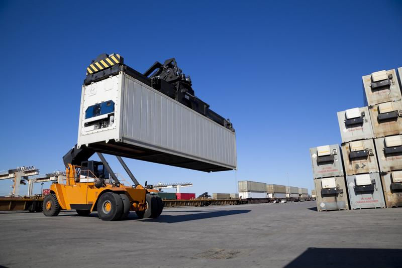A shipping container in transit in a port.