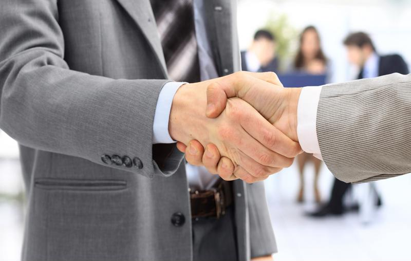 Business professionals shake hands.