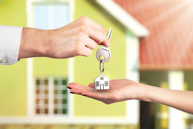 a key with a keychain of a house is being handed from on person's hand to another with an actual house in the background