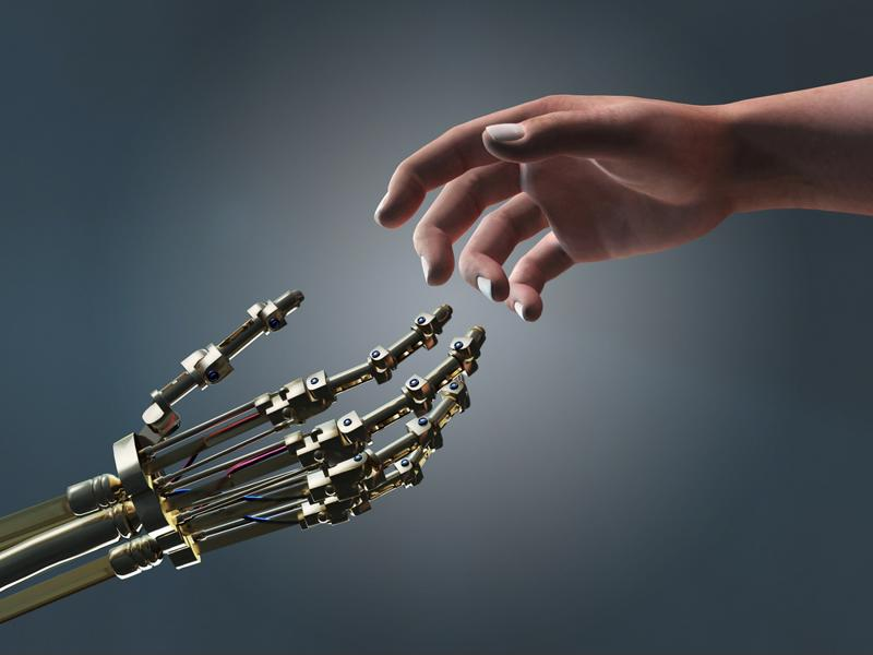 A robot hand and human hand reach out to one another.