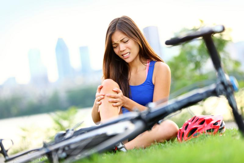 Woman holding knee after falling off bike