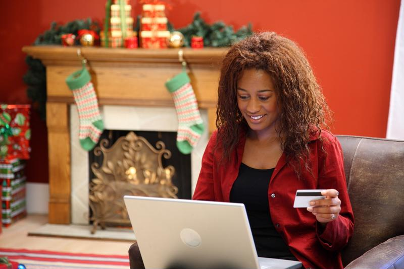 Woman with laptop holding credit card sitting in front of fireplace decorated with stockings, garland and gifts.