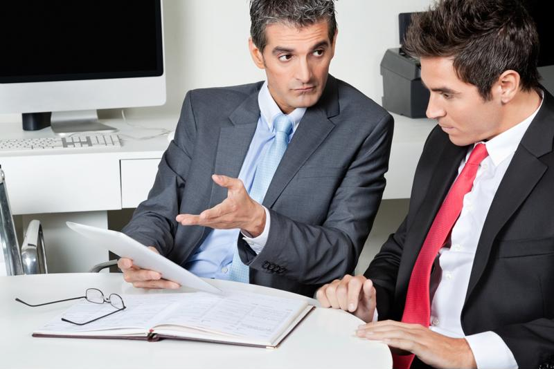 Two men discuss a business project in an office.
