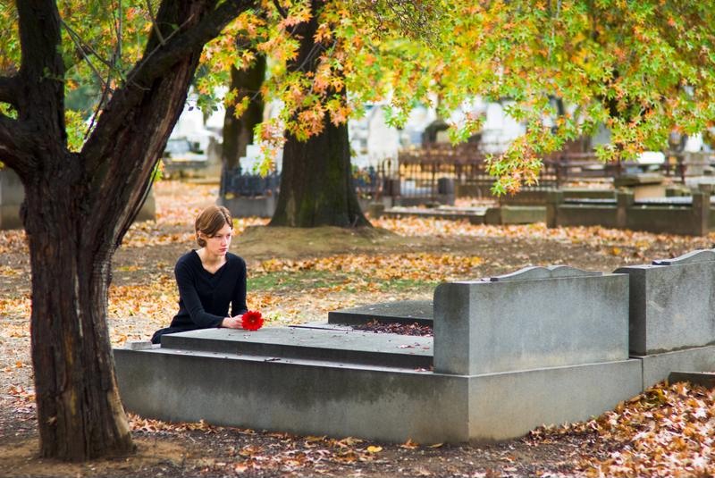 Mourning woman with flower at gravesite.
